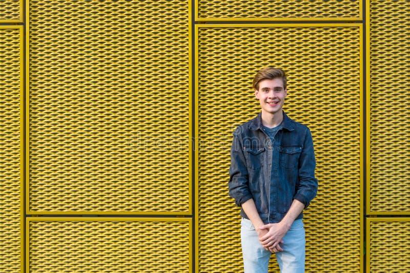 Menino adolescente à moda sobre o sorriso amarelo industrial do fundo foto de stock