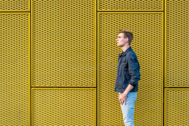 Menino adolescente à moda sobre a opinião lateral do fundo amarelo industrial foto de stock