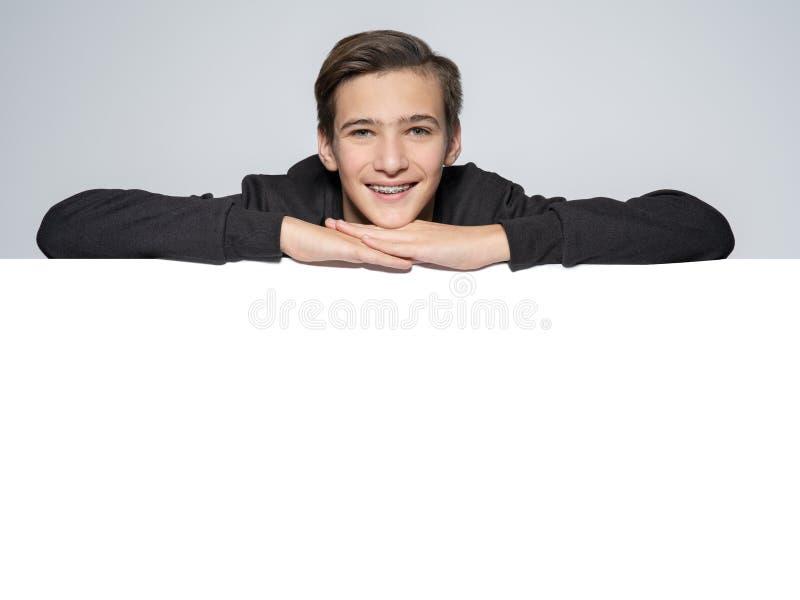 Menino adolescente acima da placa grande branca imagem de stock royalty free