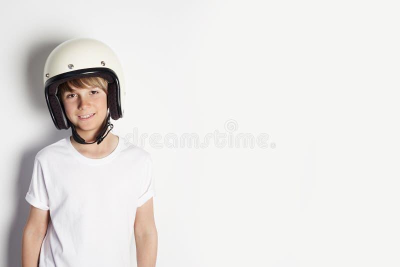 Menino adolescente alegre bonito novo feliz no tshirt branco que draming para montar uma motocicleta isolada no fundo branco foto de stock royalty free