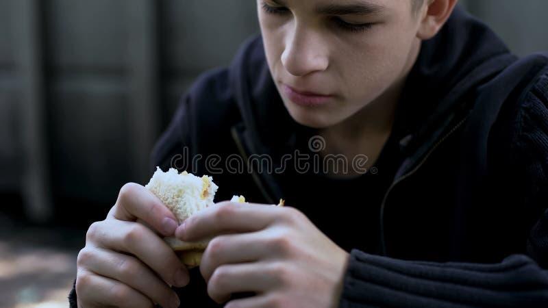 Menino adolescente com fome que come o sanduíche insalubre barato, refeição de má qualidade para a criança imagem de stock
