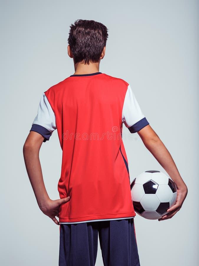 Menino adolescente da vista traseira no sportswear que guarda a bola de futebol imagem de stock