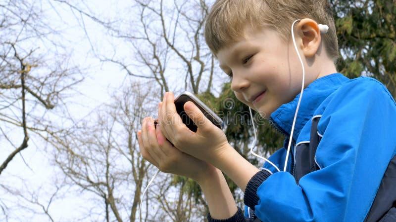 Menino adolescente de sorriso com telefone esperto que escuta ou que fala no parque britânico adolescente e conceito social dos m imagens de stock