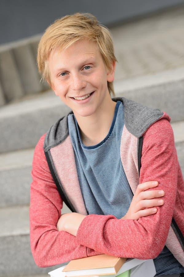 Menino adolescente de sorriso do estudante com livros fotos de stock royalty free