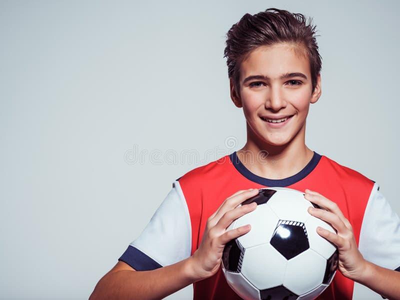 Menino adolescente de sorriso no sportswear que guarda a bola de futebol foto de stock