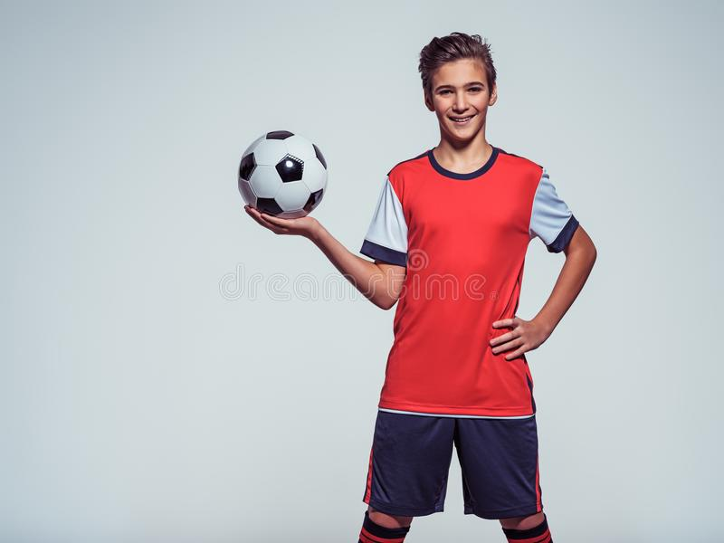 Menino adolescente de sorriso no sportswear que guarda a bola de futebol imagem de stock