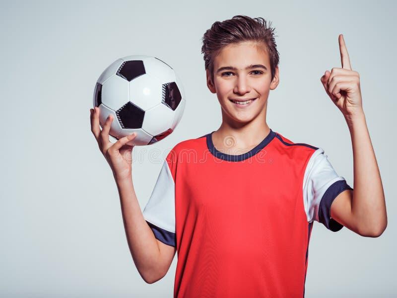 Menino adolescente de sorriso no sportswear que guarda a bola de futebol fotos de stock