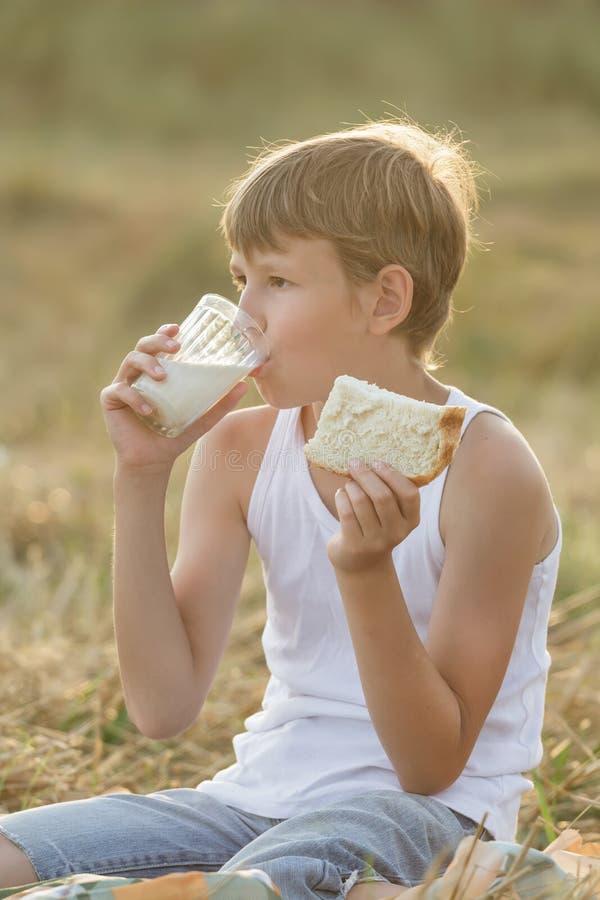 Menino adolescente do fazendeiro que aprecia o leite e o pão frescos fotografia de stock