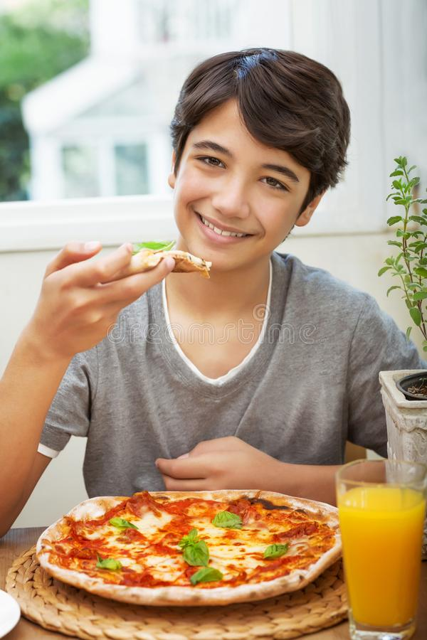Menino adolescente feliz que come a pizza fotos de stock royalty free