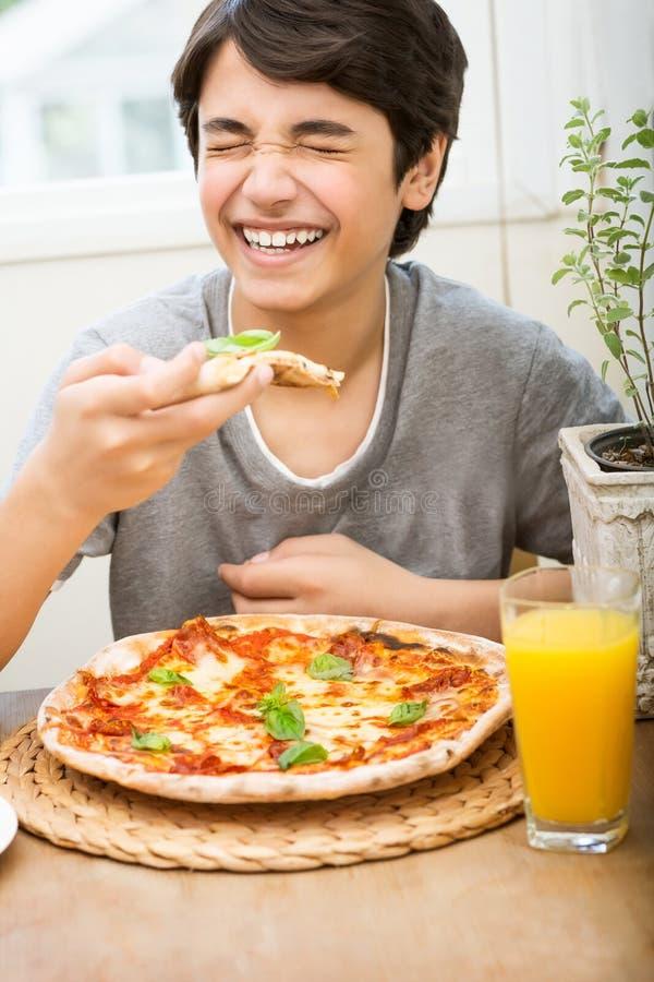 Menino adolescente feliz que come a pizza fotografia de stock royalty free