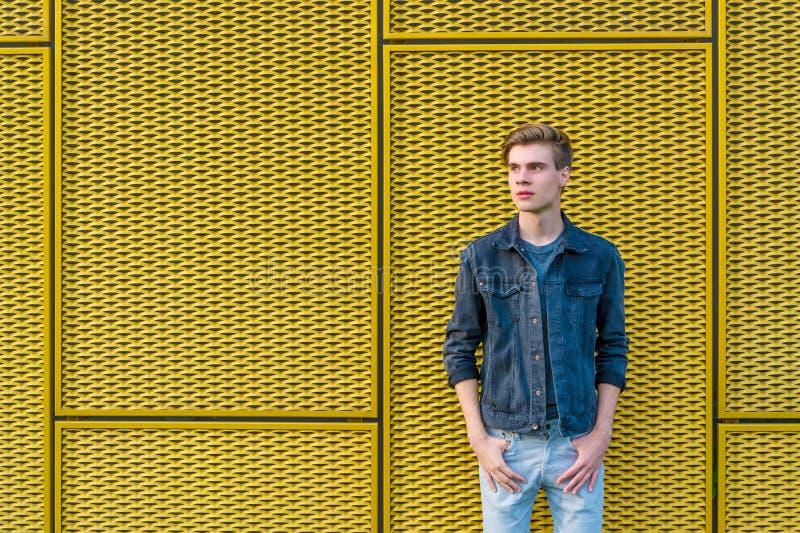 Menino adolescente pensativo sobre o fundo amarelo industrial fotografia de stock