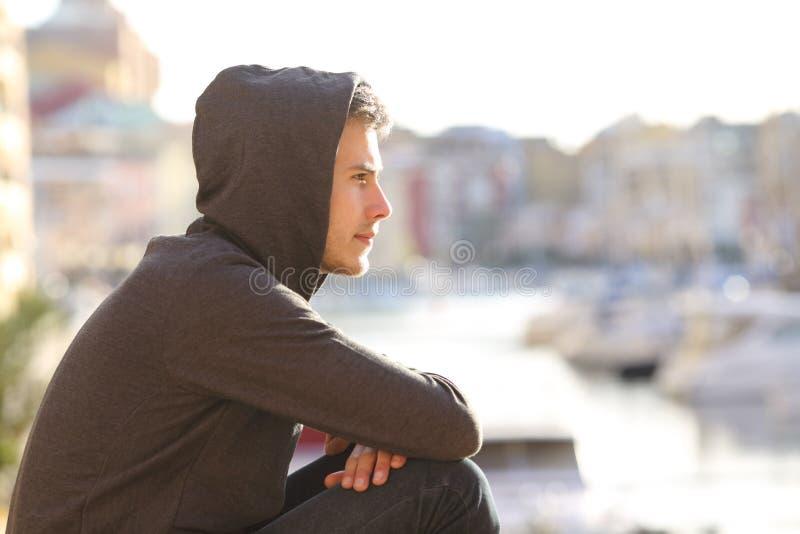 Menino adolescente que contempla um porto em férias imagem de stock