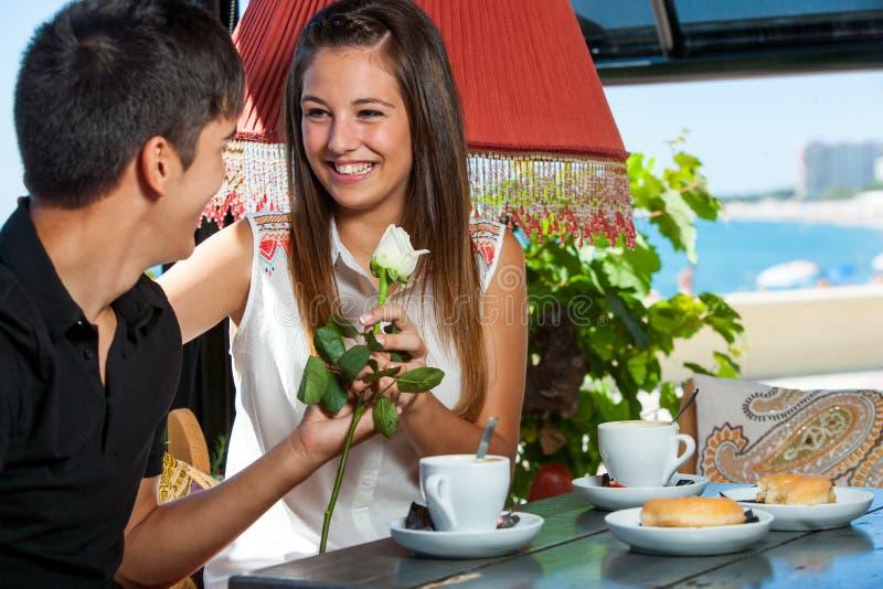 Menino adolescente que dá a flor à amiga no restaurante. fotografia de stock royalty free