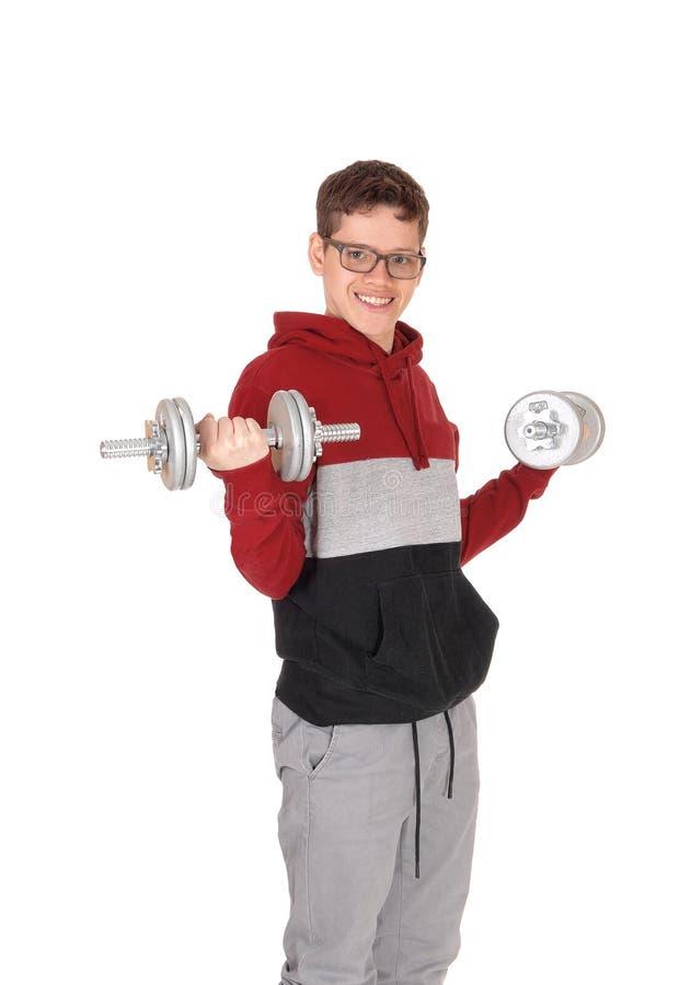 Menino adolescente que exercita com dois pesos pesados imagem de stock