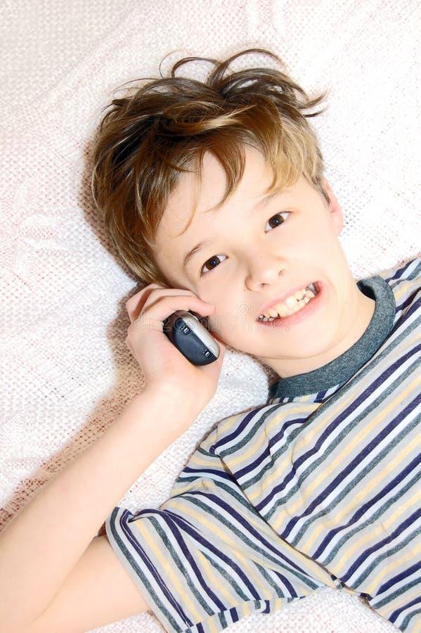 Menino adolescente que fala no telefone de pilha imagem de stock