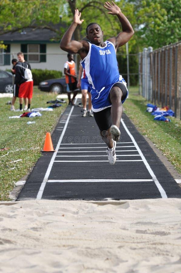 Menino adolescente que faz o salto longo na reunião do atletismo fotos de stock royalty free