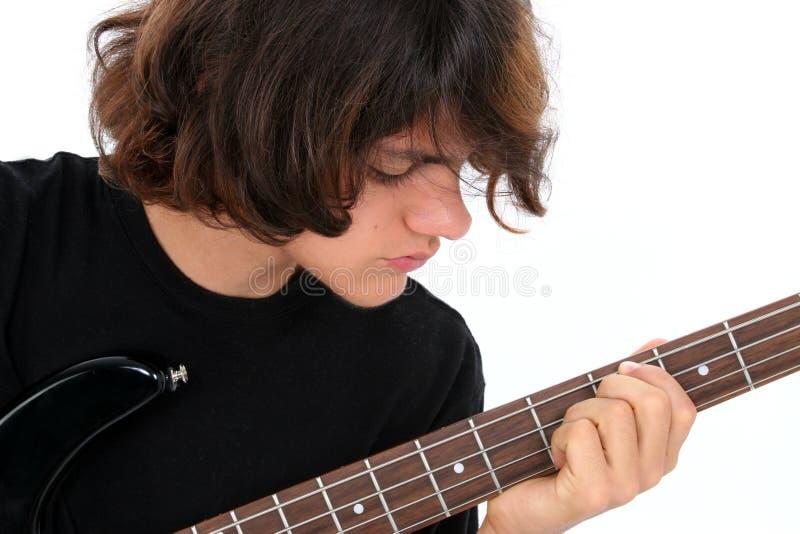 Menino adolescente que joga a guitarra baixa imagens de stock