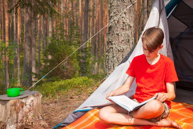 Menino adolescente que lê um livro em um acampamento da floresta do verão fotos de stock