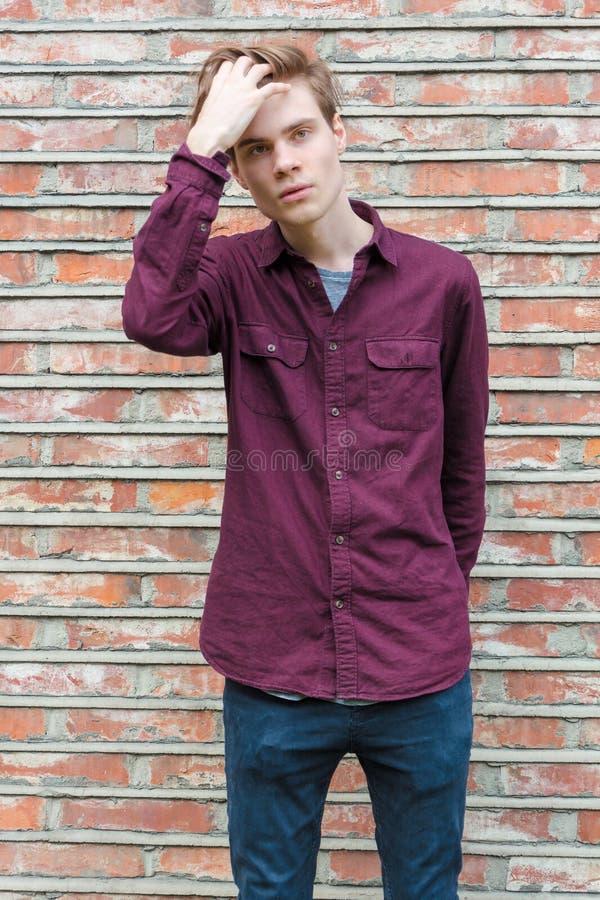 Menino adolescente que levanta sobre a parede de tijolo fotos de stock