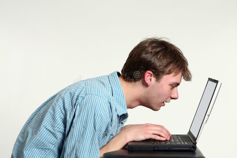 Menino adolescente que olha muito perto no ecrã de computador fotografia de stock