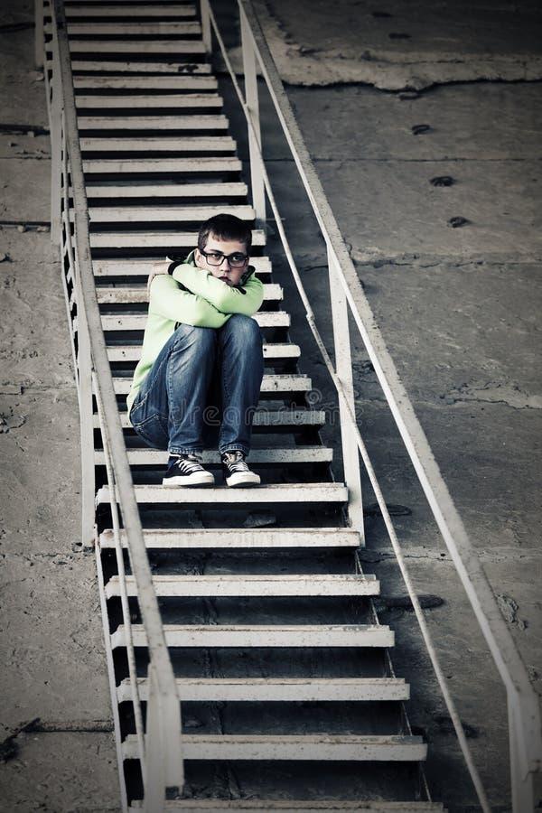 Menino adolescente triste na depressão que senta-se em etapas fotos de stock