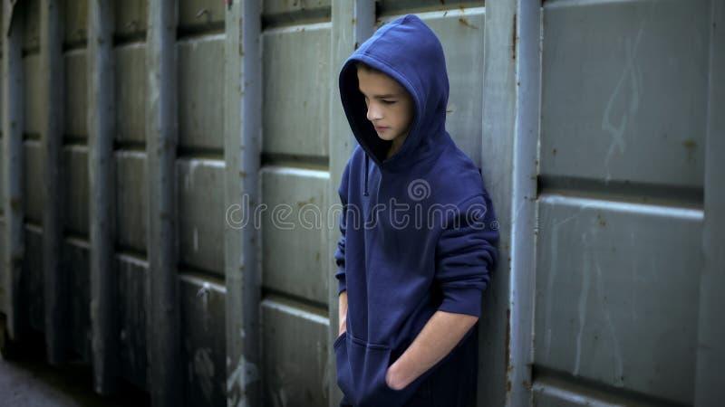 Menino adolescente triste que esconde de todos no backstreet, protesto adolescente contra a palavra foto de stock royalty free