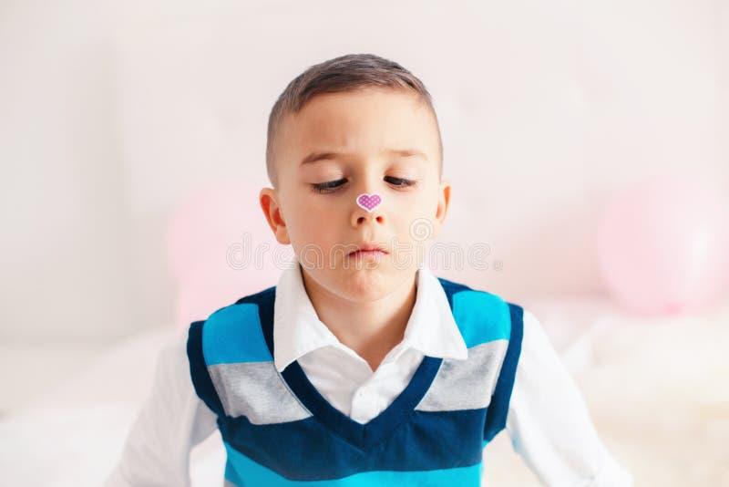 Menino adorável bonito caucasiano da criança que olha seu nariz com etiqueta do coração imagens de stock