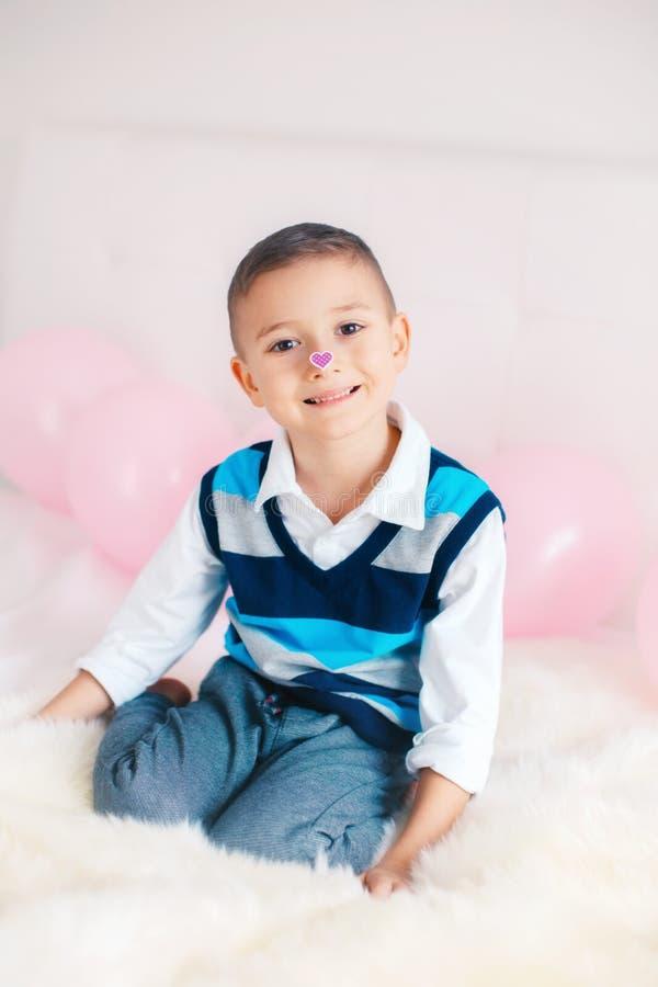 Menino adorável bonito caucasiano da criança que olha seu nariz com etiqueta do coração imagens de stock royalty free