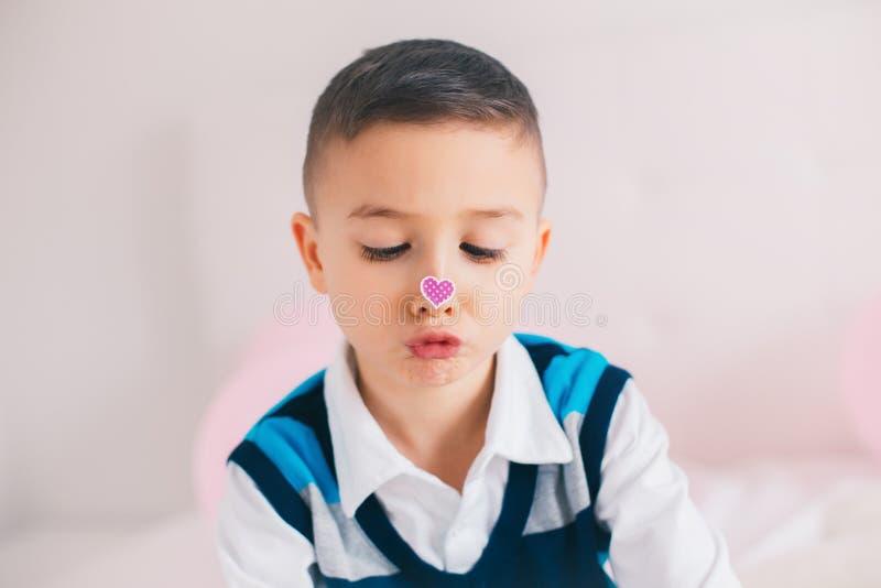 Menino adorável bonito caucasiano da criança que olha seu nariz com etiqueta do coração imagem de stock royalty free