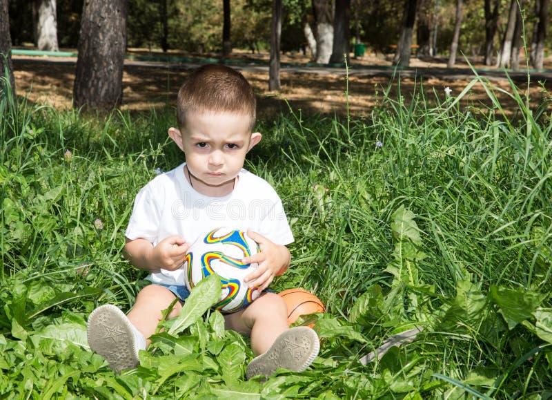 Menino adorável da criança pequena com a bola de futebol no parque na natureza no verão fotografia de stock royalty free
