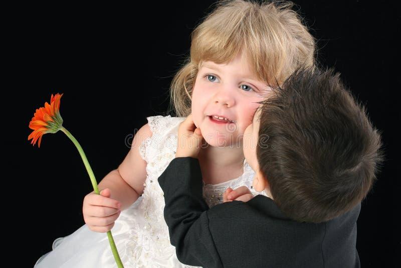Menino adorável da criança que beija a menina dos anos de idade quatro no mordente foto de stock