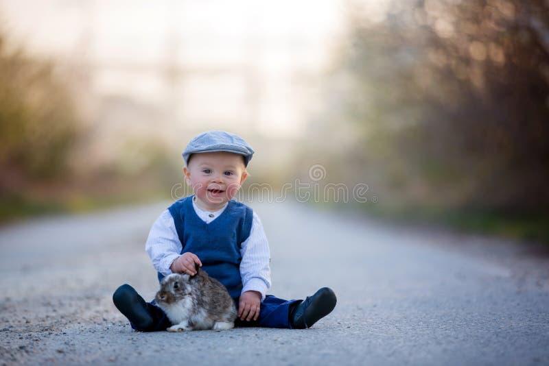 Menino adorável da criança, criança que joga com pouco coelho em um rural fotos de stock