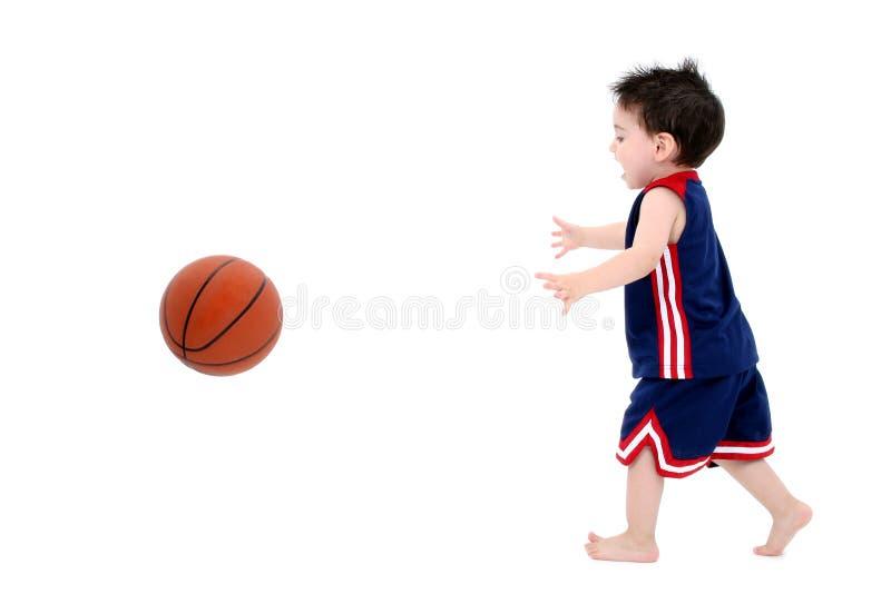 Menino adorável da criança que joga o basquetebol com os pés descalços sobre o branco imagem de stock royalty free