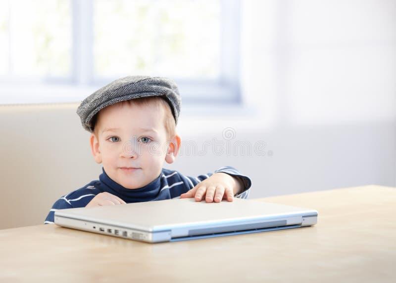 Menino adorável do gengibre no tampão que joga com portátil imagem de stock royalty free