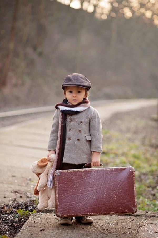 Menino adorável em uma estação de trem, esperando o trem com o urso da mala de viagem e de peluche fotografia de stock royalty free