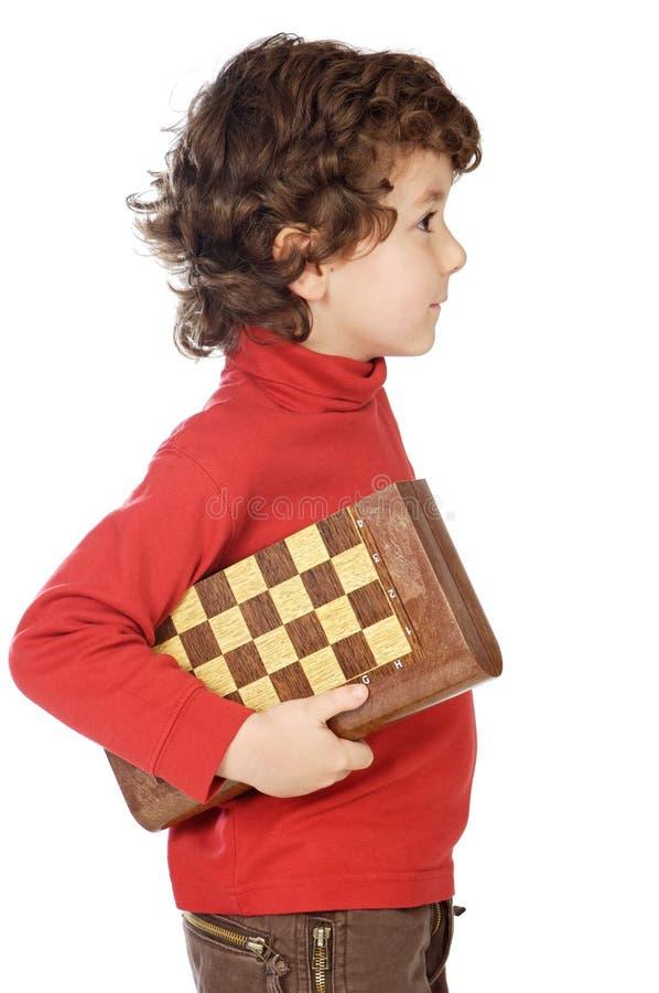 Menino adorável que joga a xadrez fotos de stock royalty free
