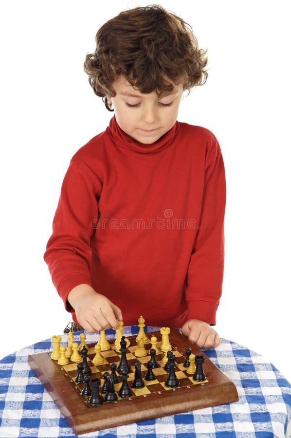 Menino adorável que joga a xadrez foto de stock