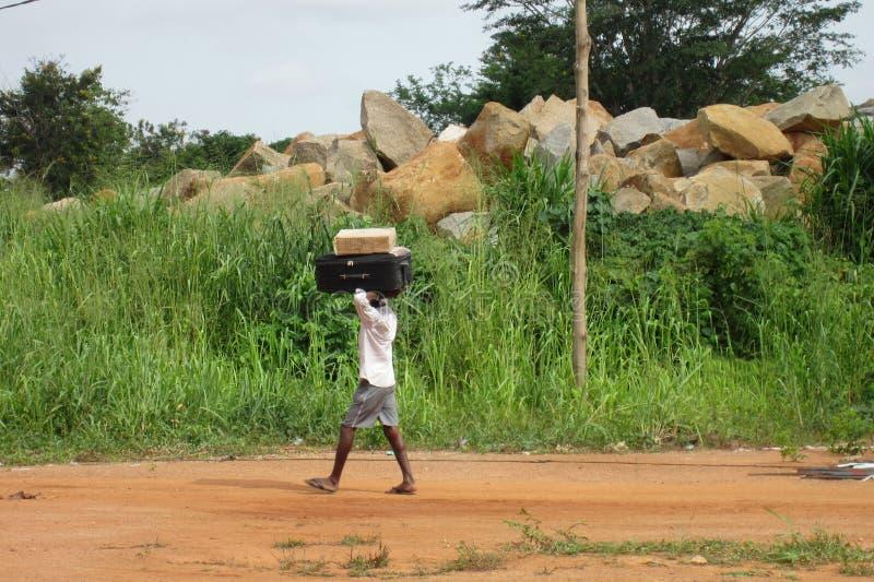 Menino africano não identificado que leva uma mala de viagem em sua cabeça imagens de stock