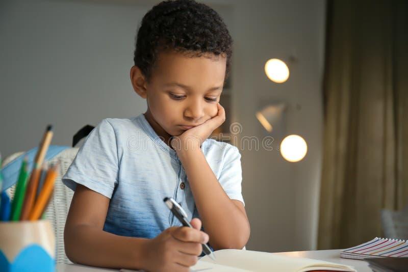 Menino afro-americano bonito que faz suas lições em casa fotos de stock