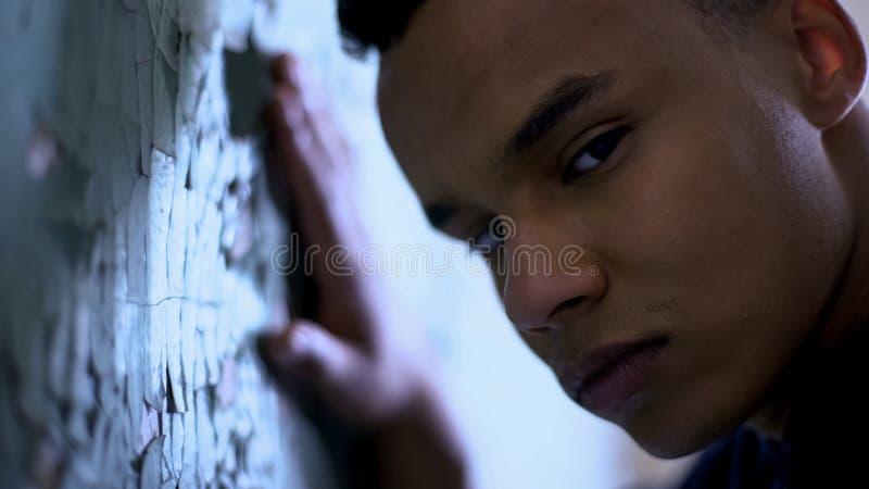 Menino afro-americano que inclina-se em dificuldades flocosos da parede, da pobreza e da vida, tristeza imagem de stock royalty free