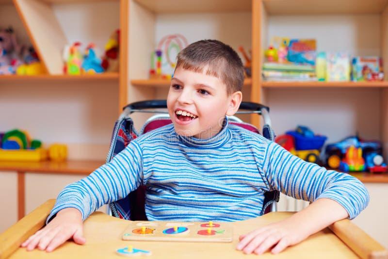 Menino alegre com inabilidade no centro de reabilitação para crianças com necessidades especiais, resolvendo o enigma lógico fotos de stock royalty free