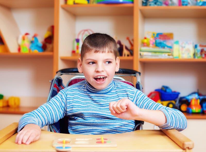 Menino alegre com inabilidade no centro de reabilitação para crianças com necessidades especiais, resolvendo o enigma lógico fotografia de stock royalty free