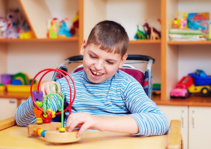 Menino alegre com inabilidade no centro de reabilitação para crianças com necessidades especiais, resolvendo o enigma lógico fotografia de stock