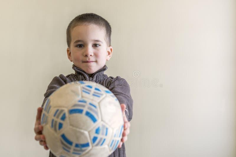 Menino alegre com uma esfera de futebol em sua mão Fundo claro Aparência europeia Copie o espaço fotografia de stock