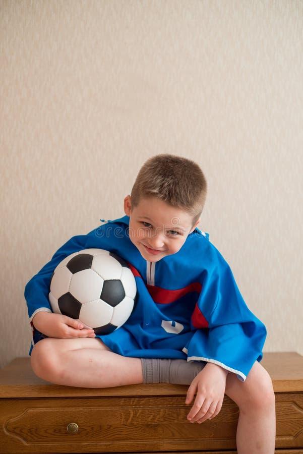 Menino alegre de riso com um futebol em um uniforme azul do esporte O fã senta-se em um futebol de observação da cadeira de madei foto de stock