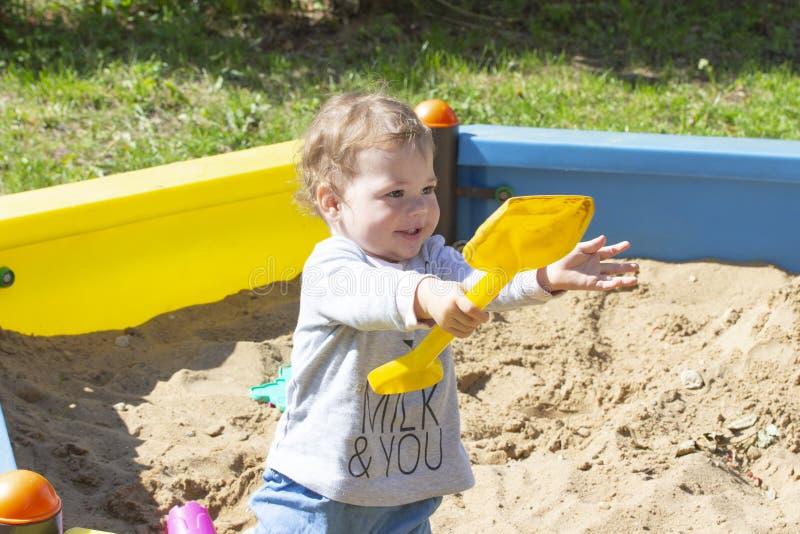 Menino alegre do bebê que joga com uma pá na caixa de areia A criança de sorriso de riso da criança da cara em uma camiseta cinze fotos de stock royalty free