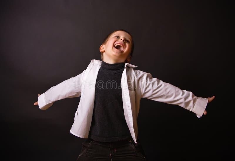Menino alegre em um fundo preto foto de stock royalty free