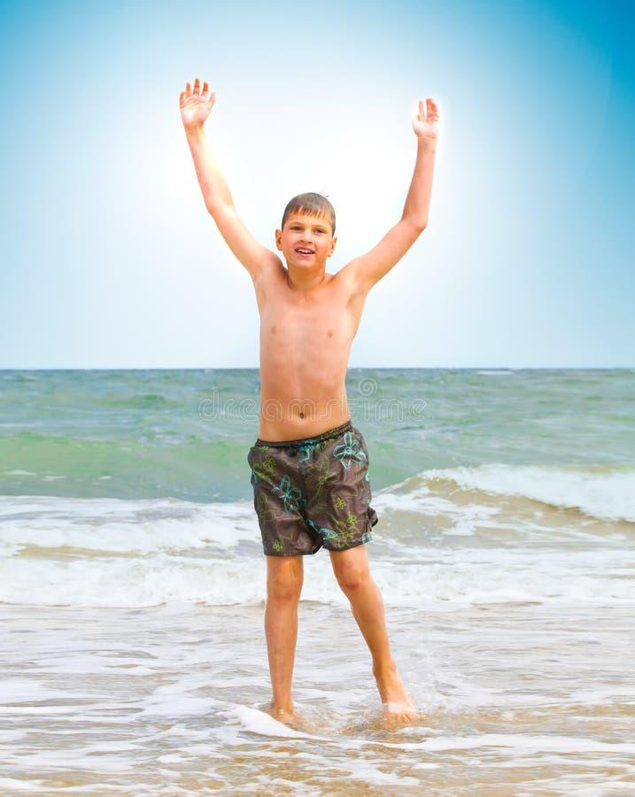 Menino alegre em uma costa do oceano foto de stock