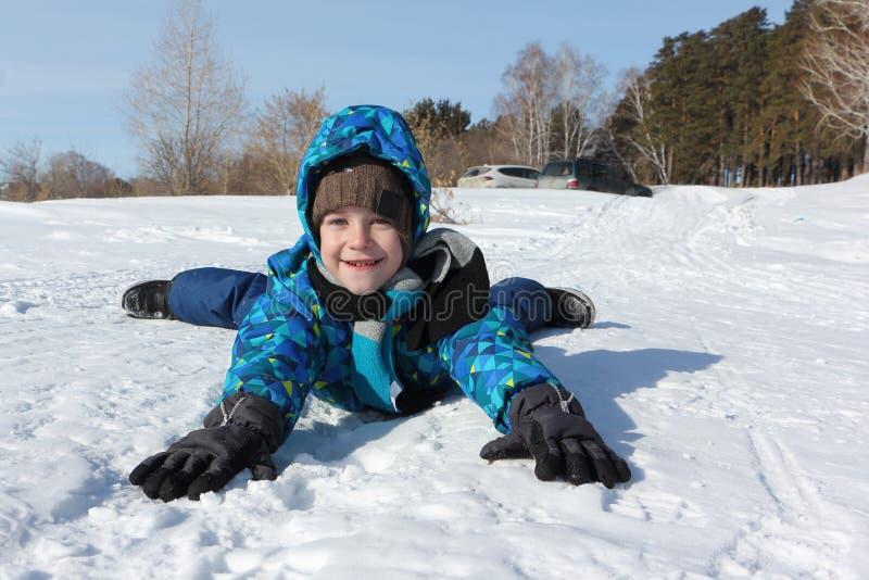 Menino alegre feliz que encontra-se na neve no inverno fotografia de stock royalty free