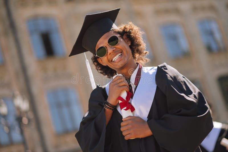 Menino alegre que abraça seu diploma na jarda de universidade imagem de stock royalty free